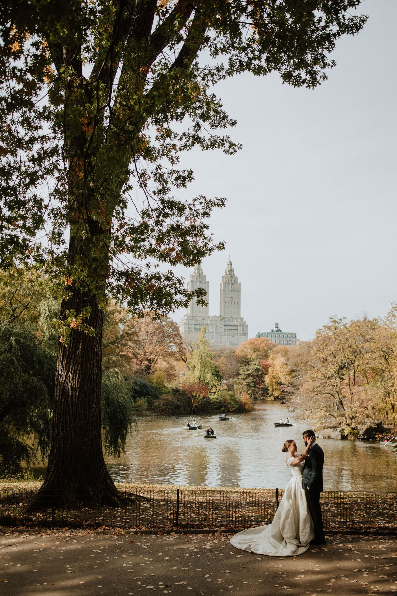 The bride and groom near the lake in Central Park, overlooking Manhatten, New York. Wedding Photographer Brent Calis.