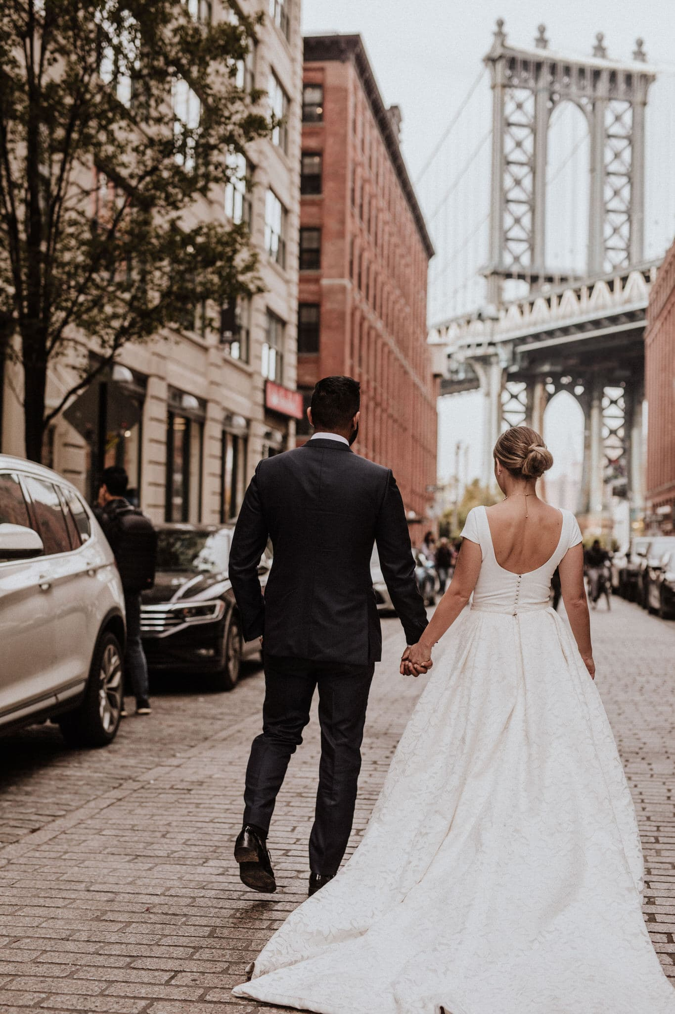 The bride and groom walk along a cobblestone street in Brooklyn, New York. Wedding Photographer Brent Calis.