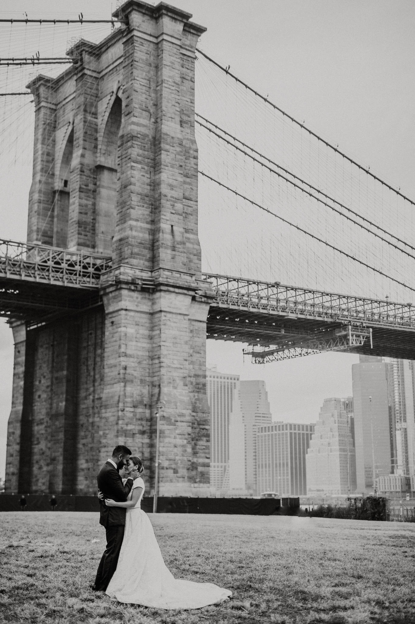 Black and white portait of the bride and groom in front of the Brooklyn Bridge Park, New York. Wedding Photographer Brent Calis.