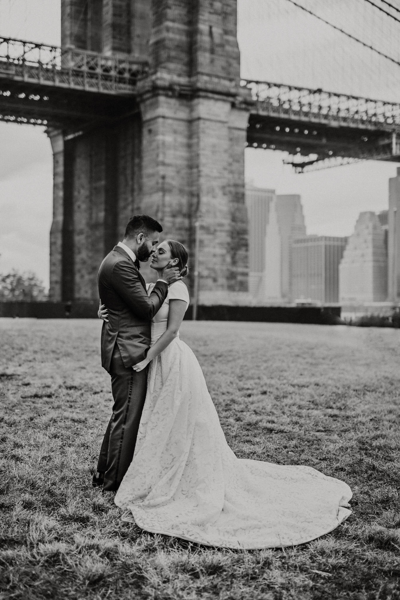 Black and white photo of the bride and groom embracing at Brooklyn Bridge Park, New York. Wedding Photographer Brent Calis.