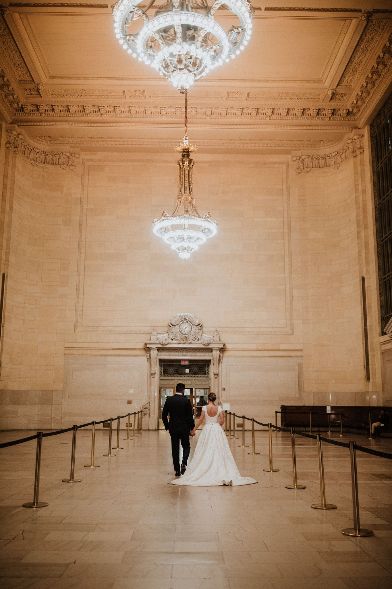 The bride and groom under the chandeliers in Grand Central Terminal, New York. Wedding Photographer Brent Calis.
