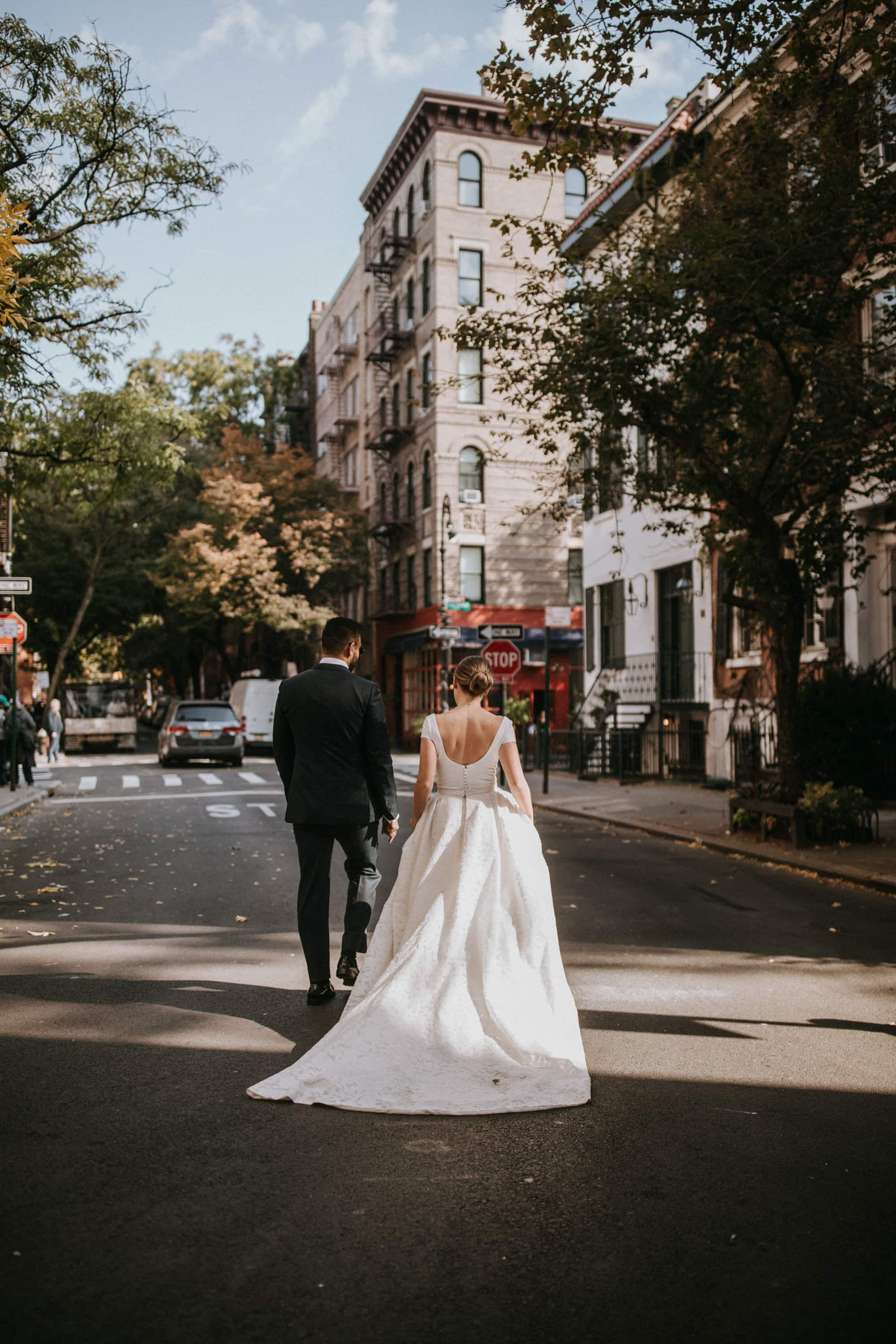 The bride and groom cross the steet in front of a red bistro on their walk through the streets of New York. In the background is the famous Friend's Apartment Building Wedding Photographer Brent Calis.