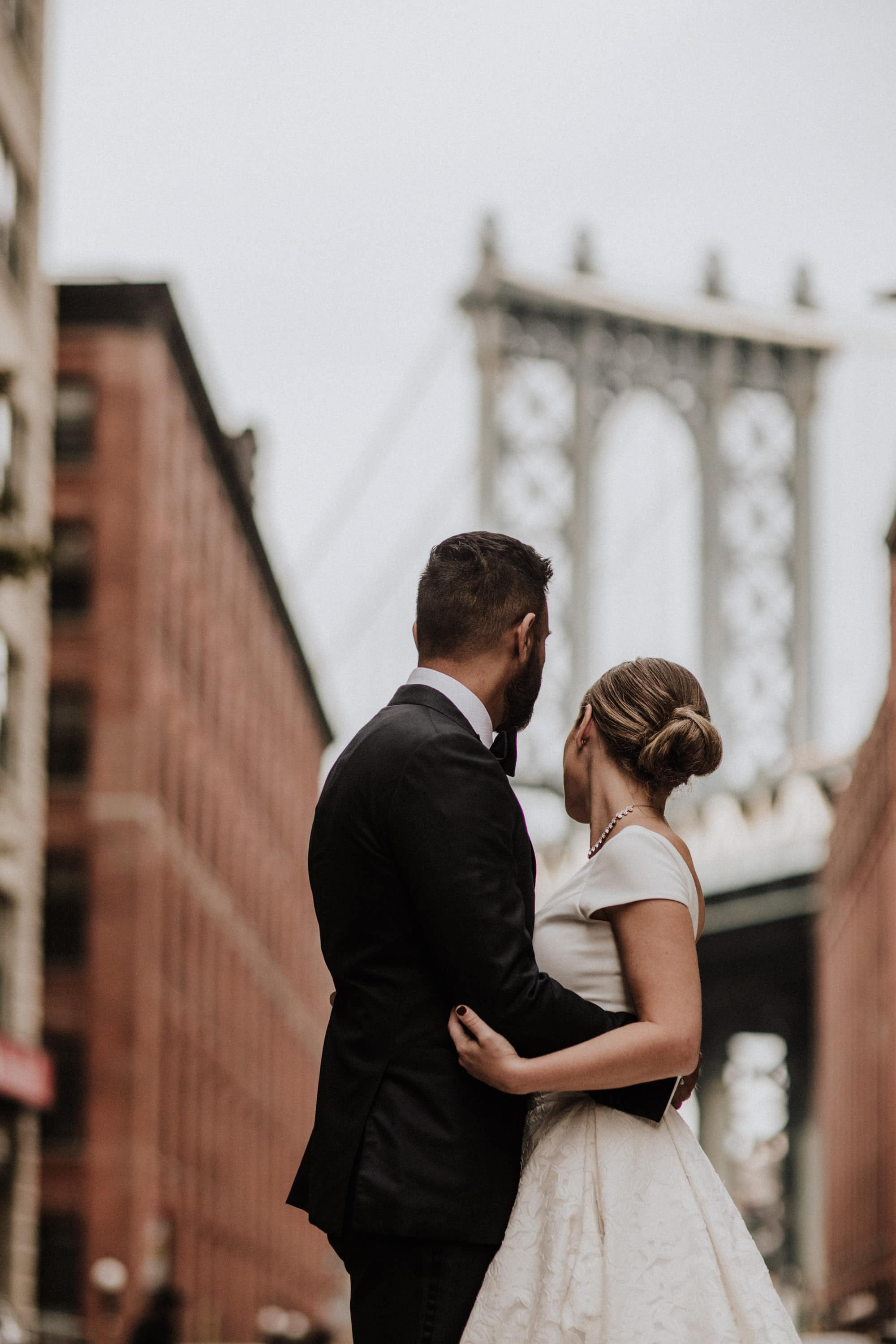 The bride and groom embrace as they look at the Manhattan bridge in the distance, in Dumbo, Booklyn, New York City. Wedding Photographer Brent Calis.