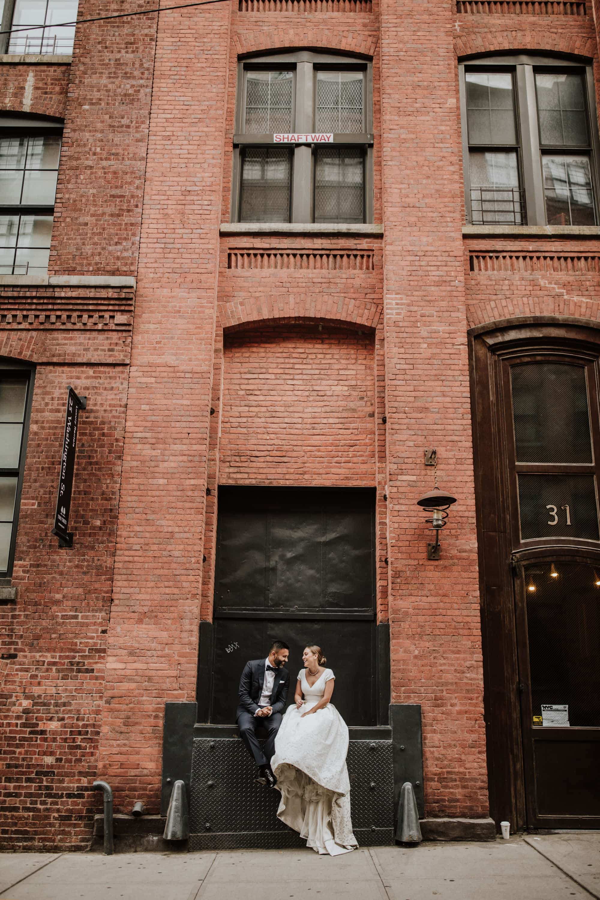The bride and groom take a break at a loading dock in Brooklyn, New York, during their New York City Elopement. Wedding Photographer Brent Calis.