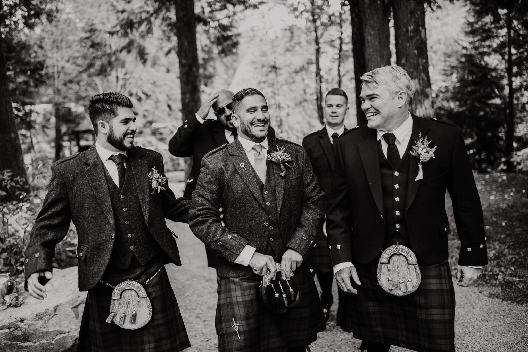 Black and white photo of groomsmen leading groom through the forest. Destination wedding photographer Brent Calis.