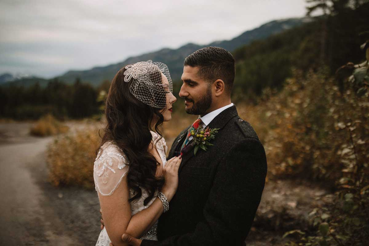 Bride and groom embrace near the mountains of Whistler. Destination wedding photographer Brent Calis.