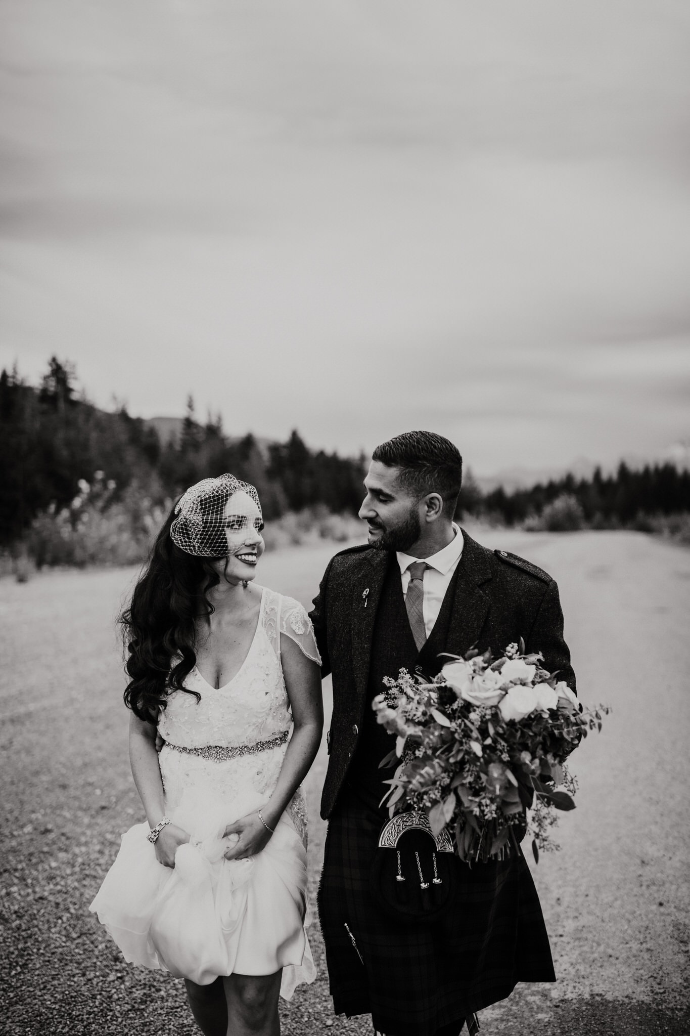 Black and white photo of the bride and groom walking near the mountains of Whistler. Destination wedding photographer Brent Calis.