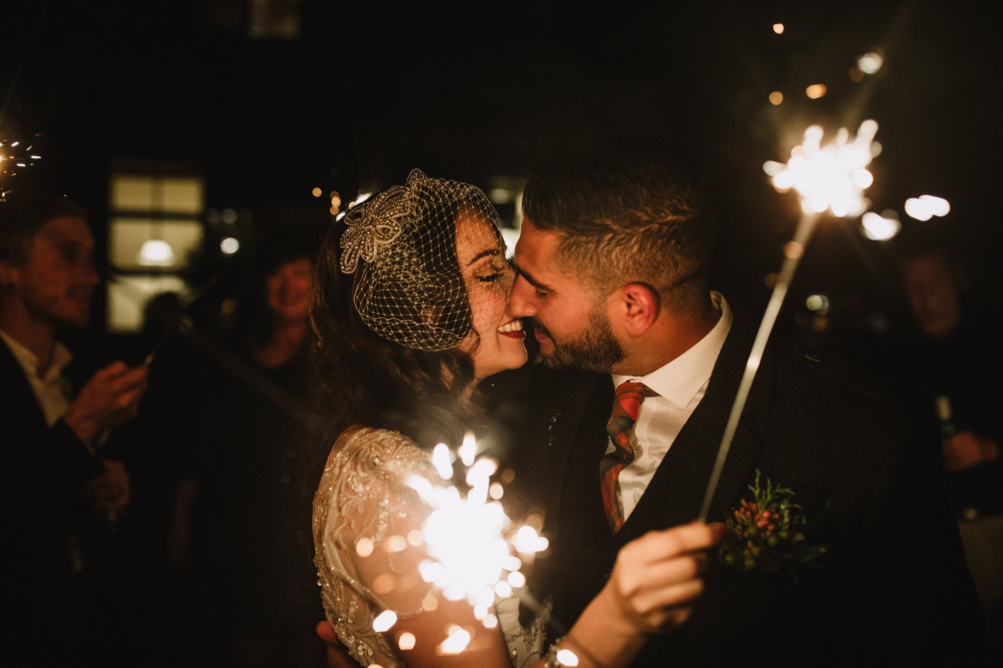 Bride and groom kiss with sparklers at Brew Creek Centre Whistler. Destination wedding photographer Brent Calis.