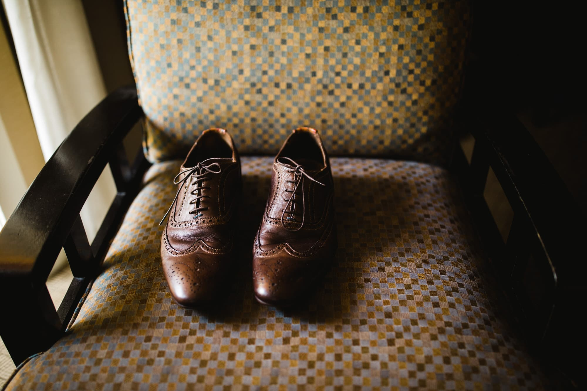 Groom's brown Oxfords shoes on chair. Destination wedding photographer Brent Calis.
