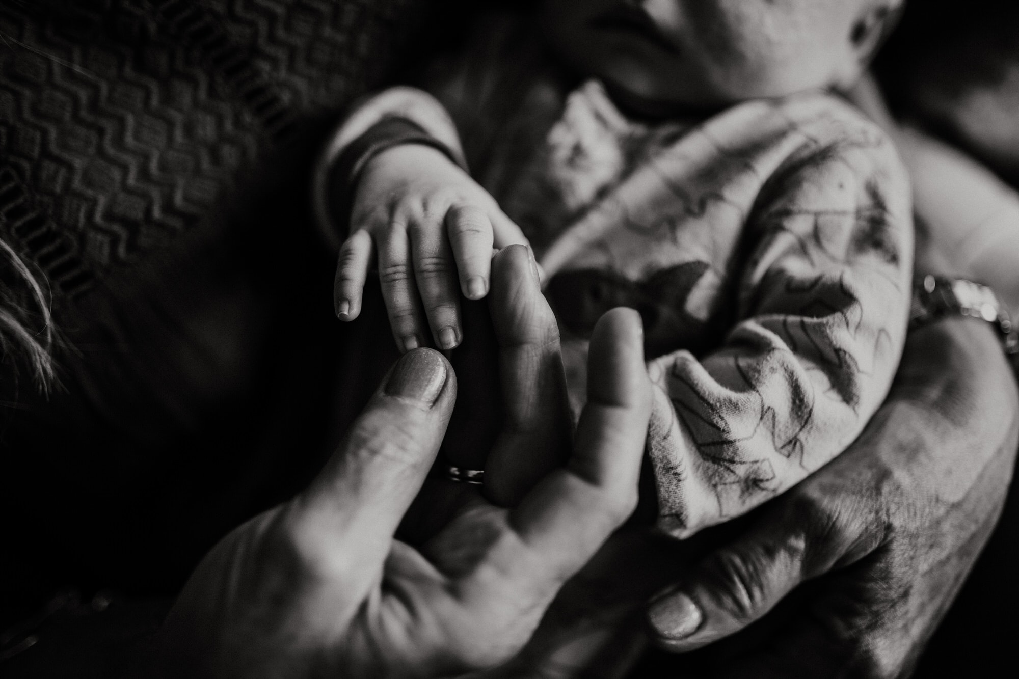 Black and white hands of grandma and baby before wedding. Destination wedding photographer Brent Calis.