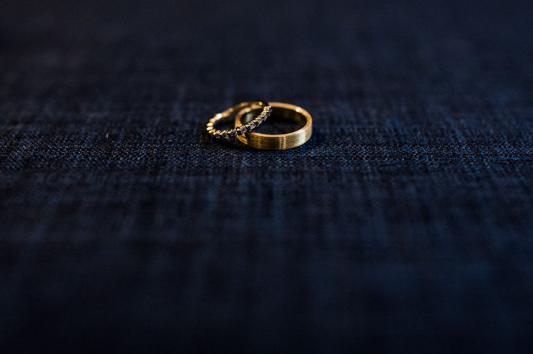 Gold wedding rings sitting on jeans. Destination wedding photographer Brent Calis.