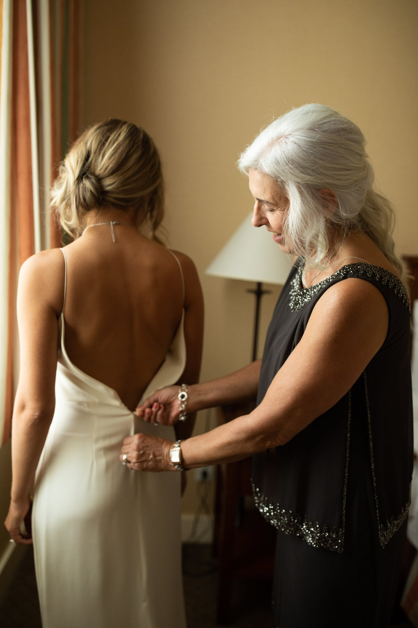 Mother of the bride helps with the dress. Destination wedding photographer Brent Calis.