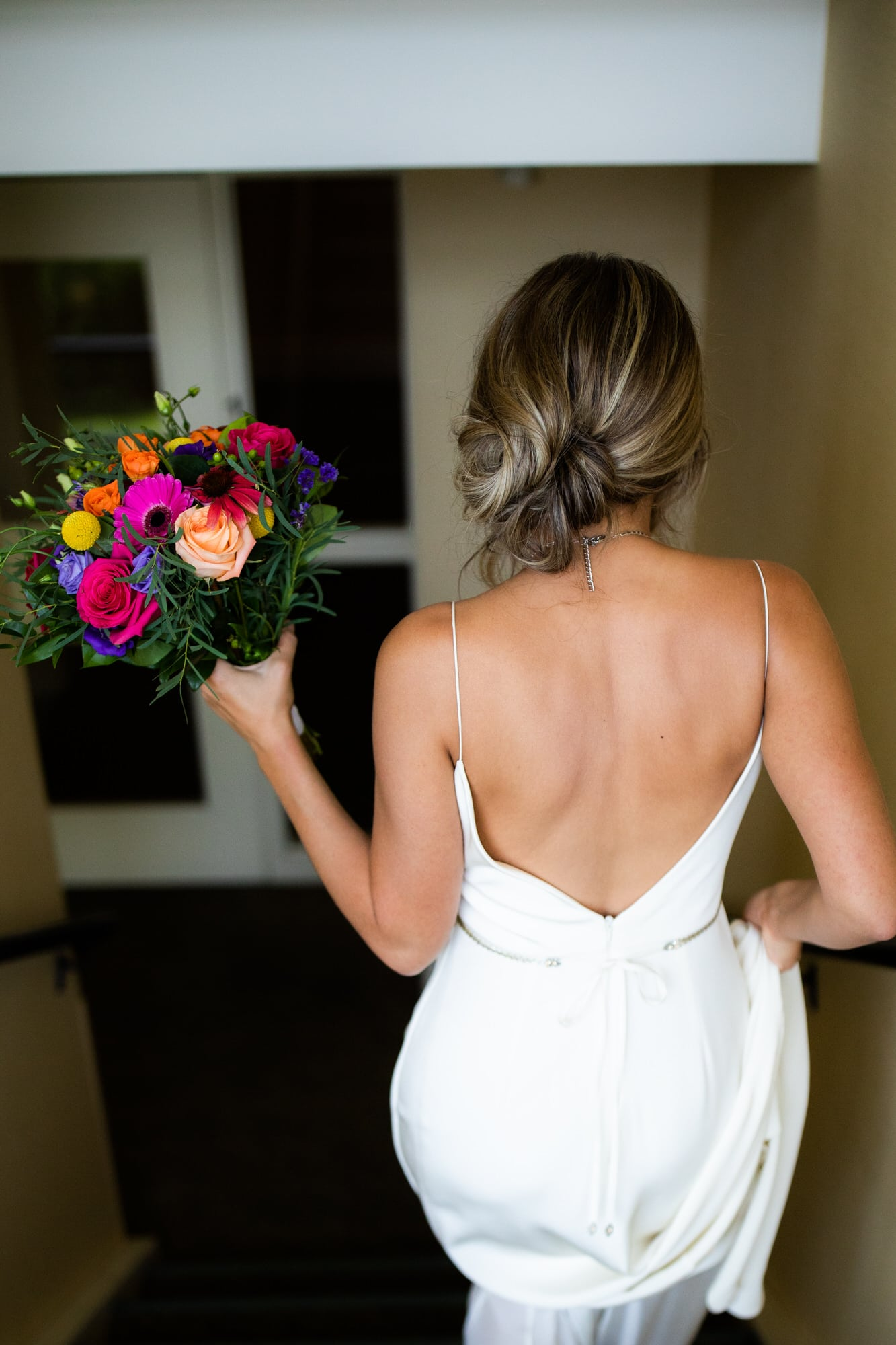 Back shot of bride walking down the stairs with boquet. Destination wedding photographer Brent Calis.