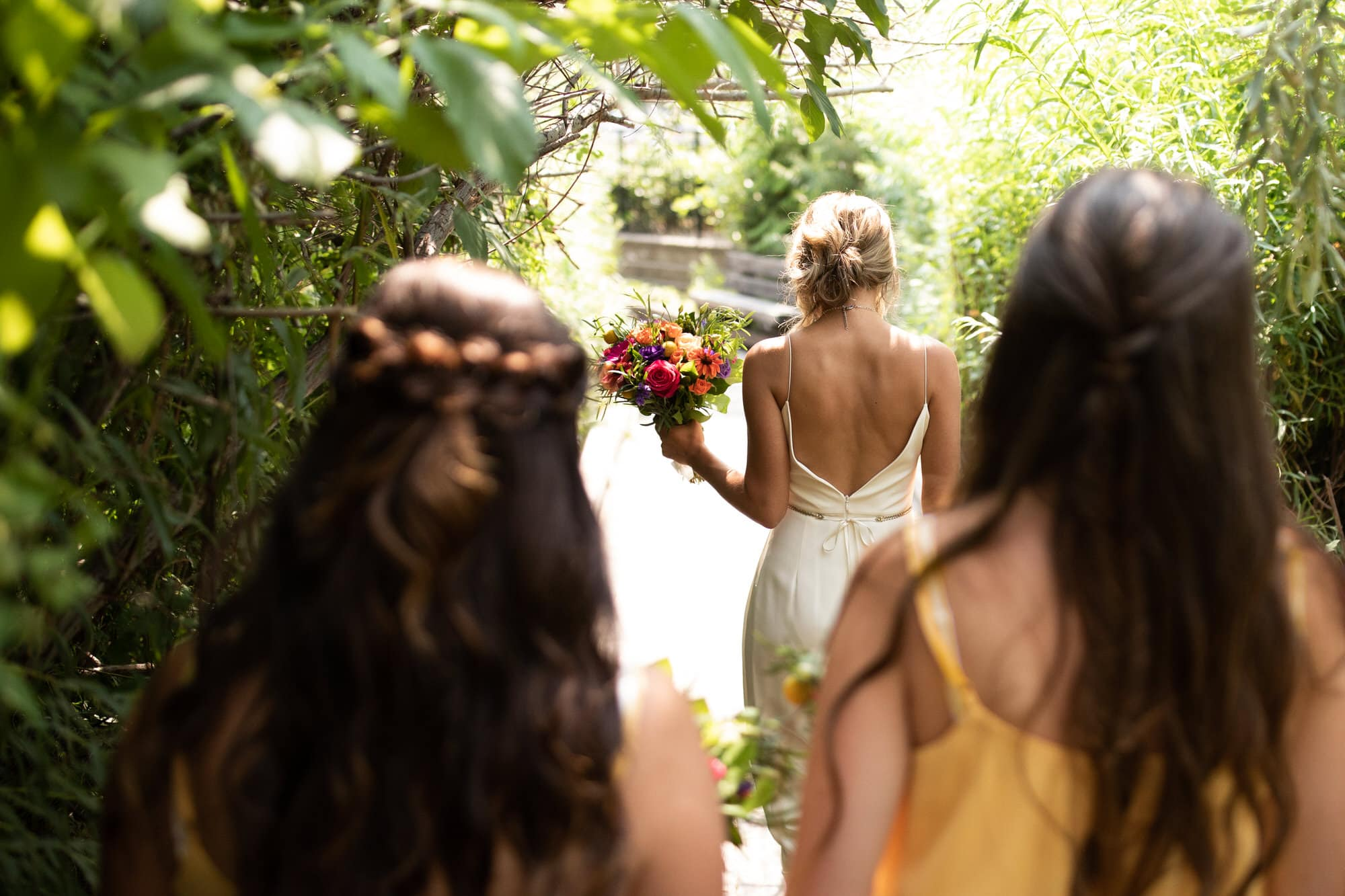 Back shot of bride and bridesmiads walking through treelined path with boquets. Destination wedding photographer Brent Calis.