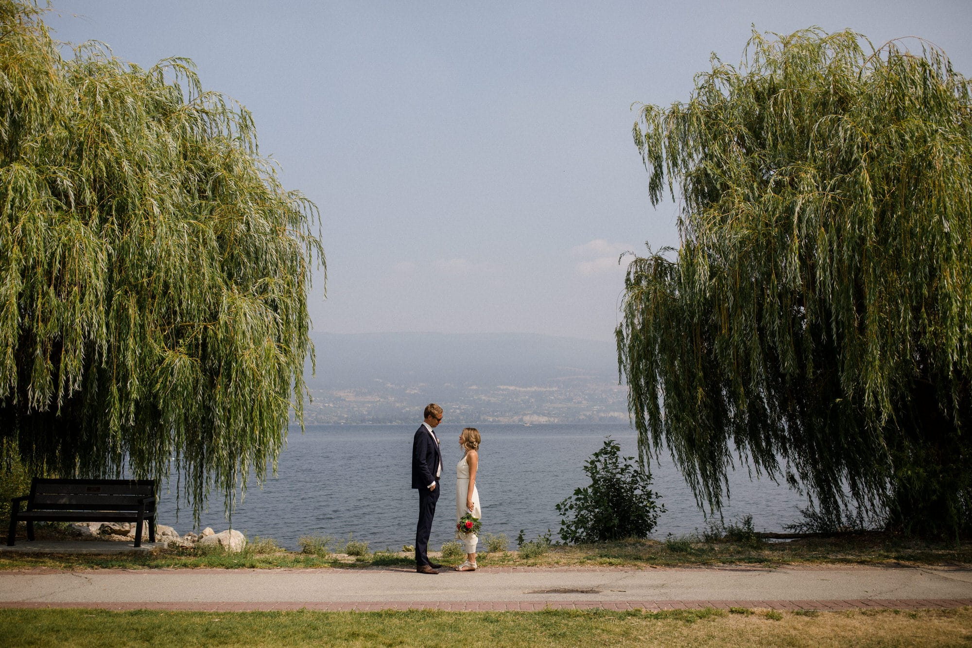 Bride and groom stand at the shore of Lake Okanagan between willow trees. Destination wedding photographer Brent Calis.