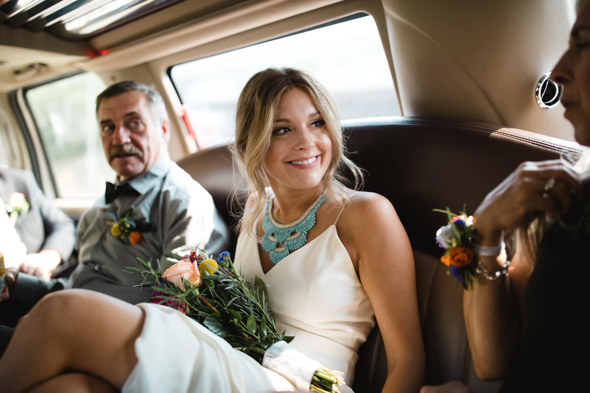 Bride smiles in the limo. Destination wedding photographer Brent Calis.
