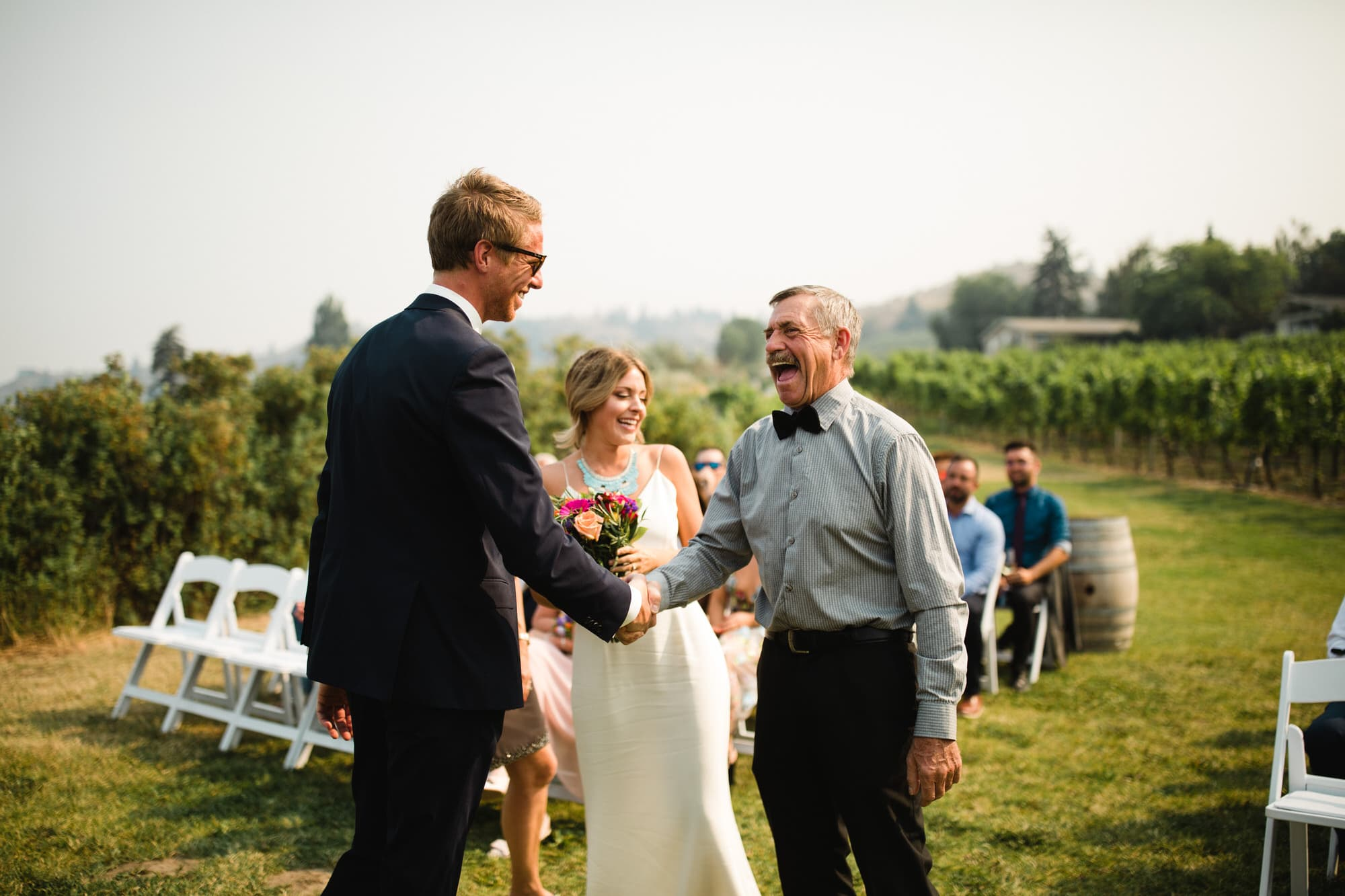 Groom and father of the bride shake hands at the alter at Evolve Cellars Vineyard on Lake Okanagan, Summerland, BC. Destination wedding photographer Brent Calis.