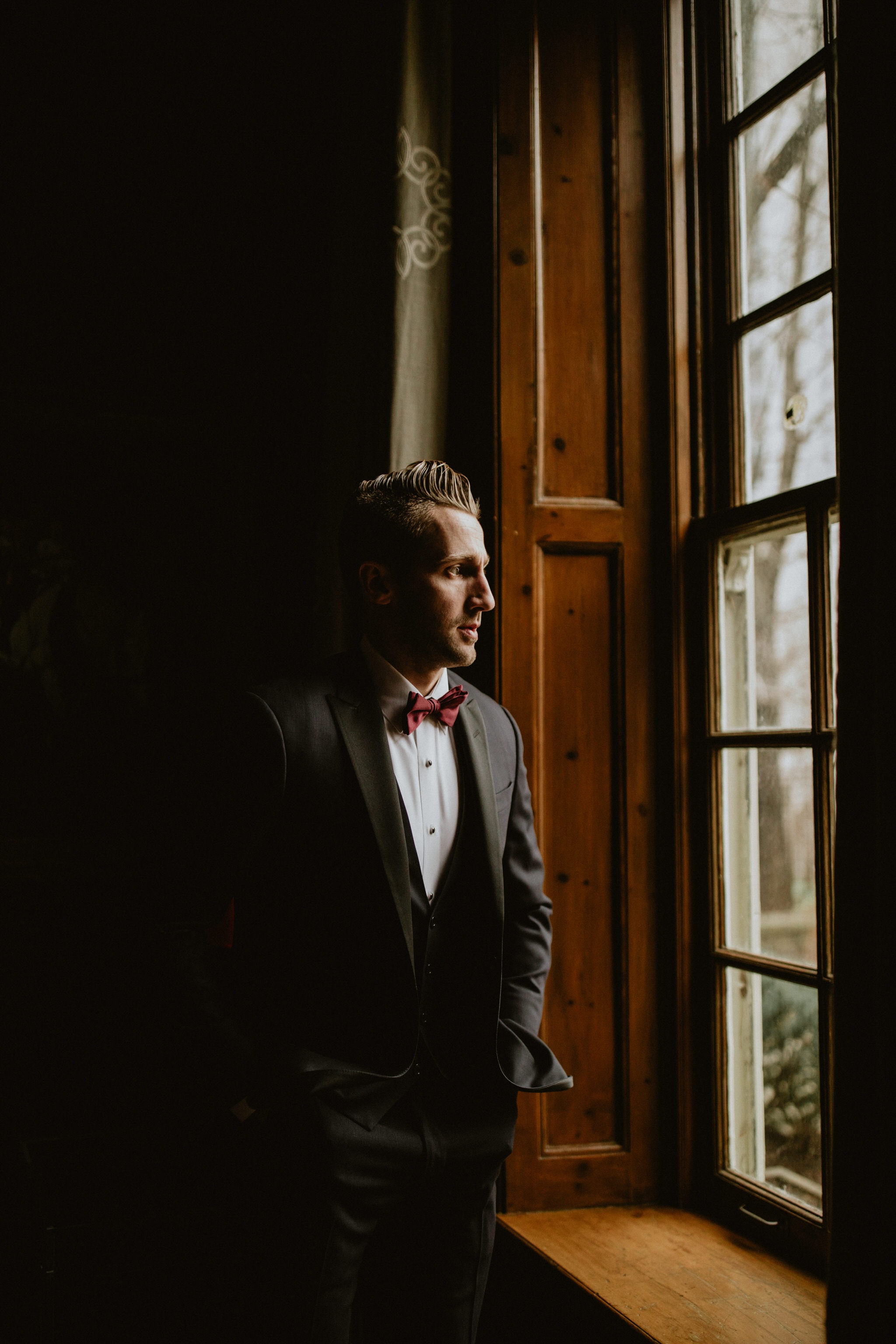 Groom waiting at the window at Graydon Hall Manor Wedding in Toronto