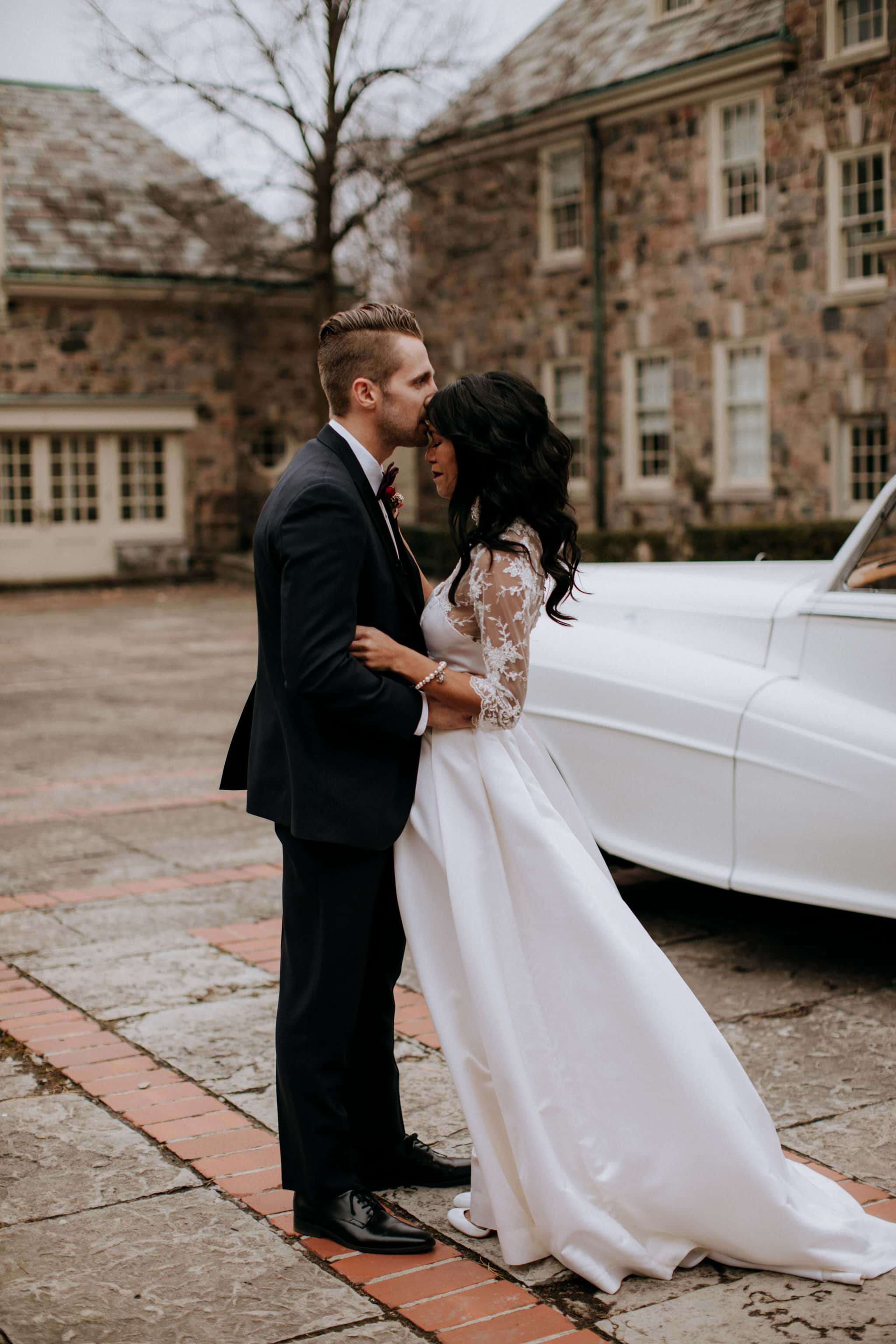 Bride and groom embrace in courtyard at Graydon Hall Manor Wedding in Toronto